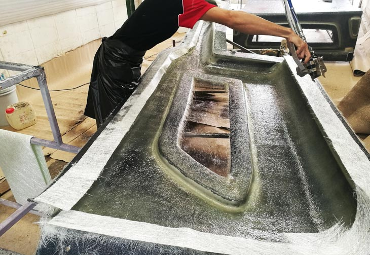 Fig. 03: A worker sprays chopped fiberglass into the resin stream for fast composite construction.